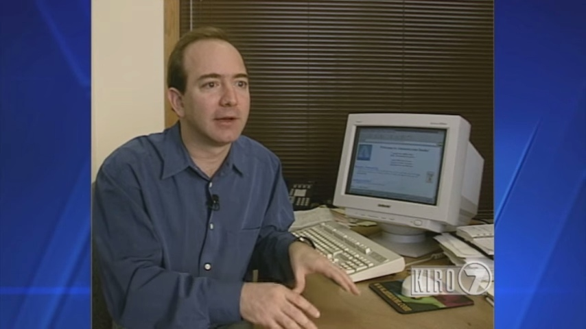 Jeff Bezos sitting at desk in front of a computer with Amazon.com in 1997